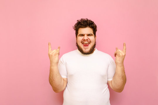 Expressive young man with an overweight and white t-shirt shows a heavy metal gesture and looks into the camera with a smile on his face. Charismatic toutsun shows rock gesture on pink background.