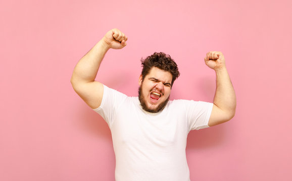 Happy fat young man shouting with joy with his hands raised on a pink background. Joyful overweight guy and white T-shirt, emotionally happy to win. Winning concept.