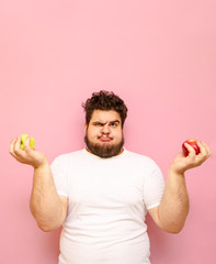Overweight funny guy stands with apples in his hands on a pink background and makes a funny face wearing a white T-shirt. Vertical photo of a funny fat man making a funny face with fruits in hands.