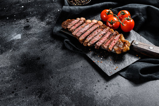 Grilled sliced strip loin steak on a meat cleaver. Black background. Top view. Copy space