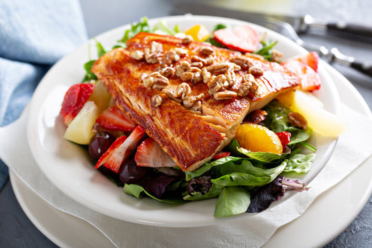 Fresh and vibrant salad with salmon, green leaves and fruit
