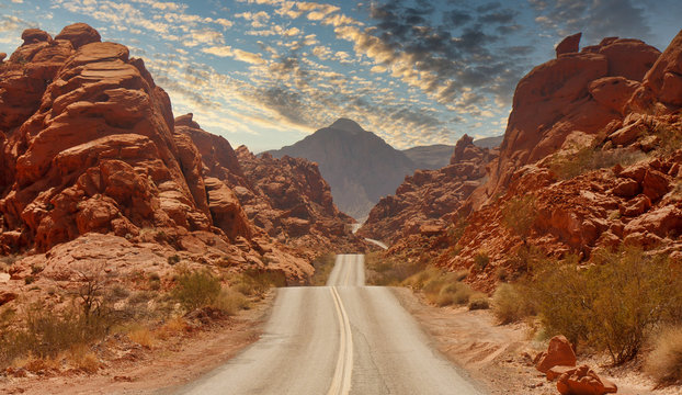A highway rolling through red rock canyons in Nevada