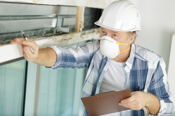 mature man inspecting property wearing face mask