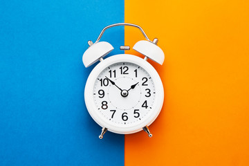 Photo sur Toile Retro White vintage alarm clock on blue-orange background. Top view, copy space. Daylight saving concept.