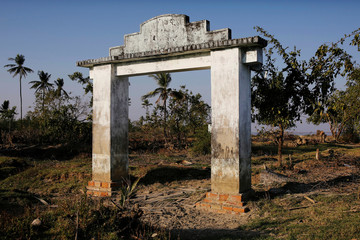 The remnants of an archway of a school is seen after the river bank it was located on collapsed into the water in Ta Dar U village, Bago, Myanmar