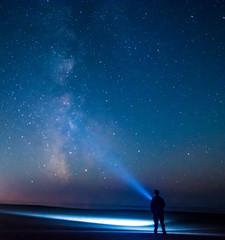 Adventurous man watching the stars on a beach at night.