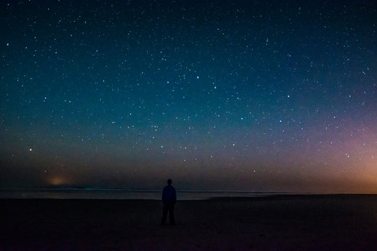 Adventurous man watching the stars on a beach at night.