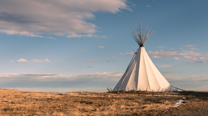 Fototapeta Traditional Native American nomadic teepee in the grassy plains at sunset and beautiful landscape background obraz