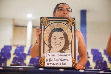 A woman holds a picture of her mother during a congress session to protest against the approval of an amnesty bill that exempts the prosecution of crimes committed during the civil war, in San Salvador, El Salvador