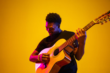 Young and joyful african-american musician playing guitar and singing on gradient orange-yellow studio background in neon light. Concept of music, hobby, festival. Colorful portrait of modern artist. Wall mural