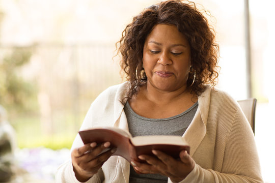 Mature African American woman sitting outside reading.
