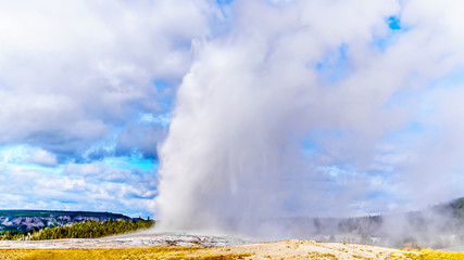 Eruption of the famous Old Faithful Geyser a Cone Geyser in the Upper Geyser Basin along the Continental Divide Trail in Yellowstone National Park, Wyoming, United States