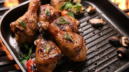 Fototapete - Close up grill roast bbq chicken leg with addition herbs and spices on the frying pan on the flaming grill . 4k