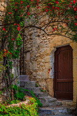 Old wooden door of a stone house covered with flowers in South of France Eze Village, medieval city...