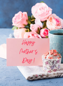 Happy mothers day greetings. Holiday greeting card with lettering text, cup of tea and cupcake