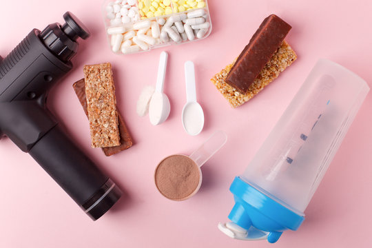 Therapeutic percussive massage gun, fit meal, pills, sport energy bar on pink background - concept of modern sport activity and diet, health lifestyle routine, wellness, healthcare, copy space