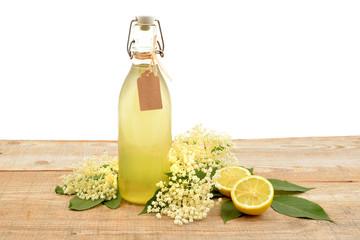 Homemade elderflower syrup in a bottle with flower (Sambucus nigra) and lemon isolated on white background.