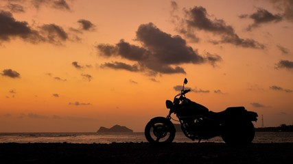 Foto op Canvas Fiets Motorcycle silhouette at sunset time near sea coast line