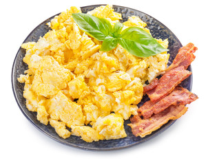Plate with scrambled egg and bacon on white background