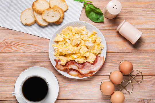 Plate with scrambled egg and bacon on table