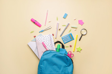 Set of school supplies with backpack on color background