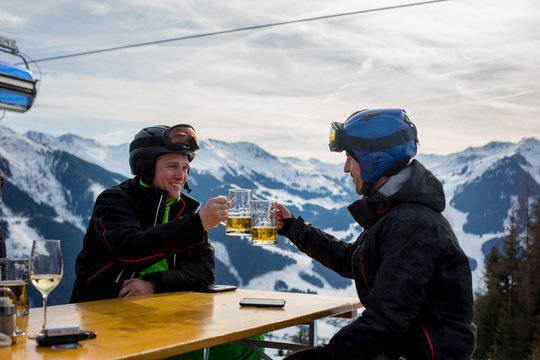 Middle aged men, drinking beer in a restaurant, while having break from skiing