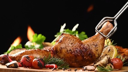 Wall Mural - Close up grill roast bbq chicken with addition herbs and spices on the on the flaming grill . slow motion