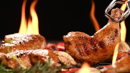 Fototapete - Close up grill roast bbq chicken with addition herbs and spices on the on the flaming grill . slow motion