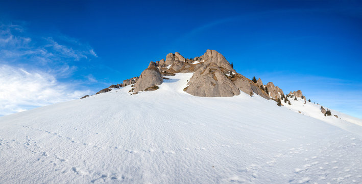 Panoramic view of Mount Ciucas peak covered in snow at sunset on winter