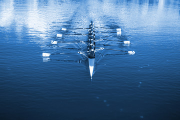 Boat coxed eight Rowers rowing on the tranquil lake. Classic Blue Pantone 2020 year color. Fotomurales