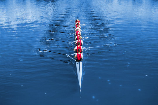 Boat coxed eight Rowers rowing on the blue lake. Classic Blue Pantone 2020 year color.