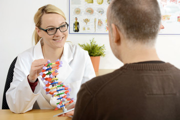 Doctor works as a geneticist and gives a patient a genetic consultation in her treatment room