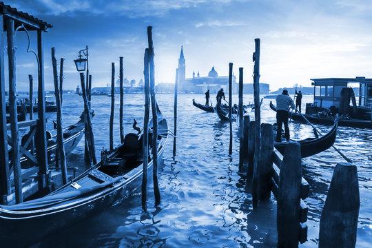 Venetian Gondolas in Italy, sunset behind San Giorgio Maggiore church. Classic Blue Pantone 2020 year color.