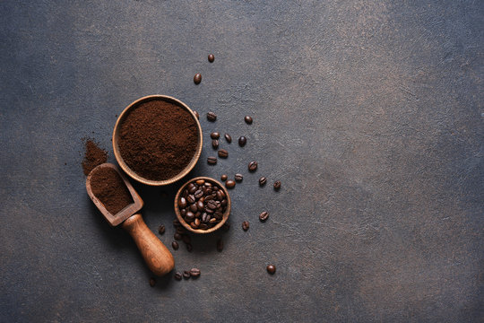 Coffee beans and ground coffee on a concrete table.