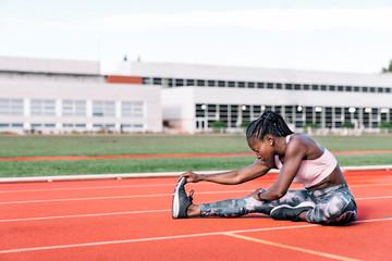 Athlete sprinter stretching her legs