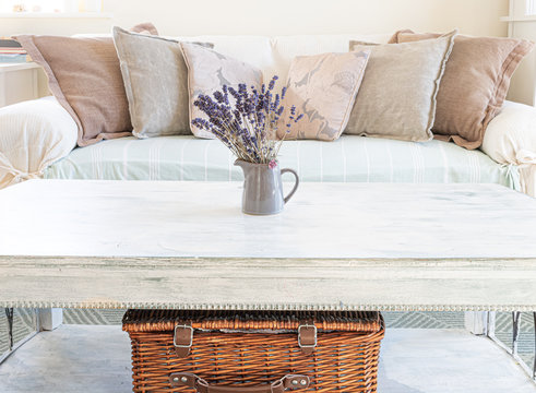 spring table decoration in a cozy living room, wicker basket, pillows, leaves pumpkin, butternut squash, autumn leaves, orange colour, arrangement,rustic table and sofa with blanket, nordic style