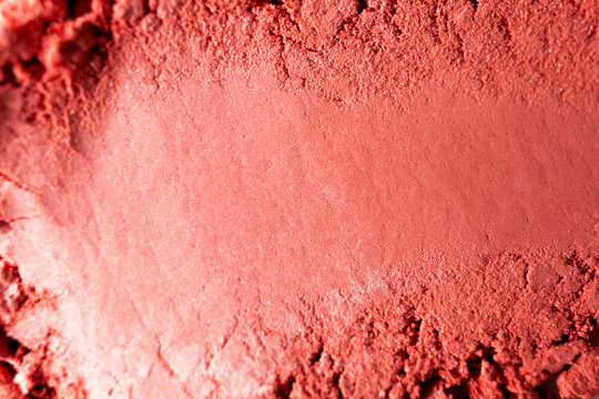 Red blush close-up texture with selective focus. Macro makeup product. Beauty background or backdrop