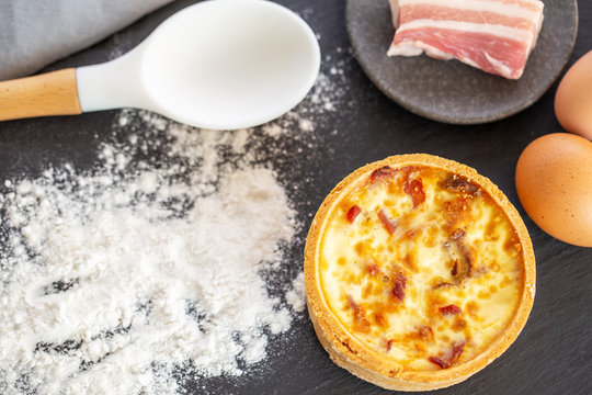 Quiche Lorraine flat lay, with spilled flour, bacon, eggs and spoon on a slate.