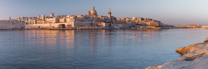 Wall Mural - Panorama of Valletta with Our Lady of Mount Carmel church and St. Paul's Anglican Pro-Cathedral at sunrise as seen from Sliema, Valletta, Malta