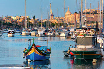Fototapete - Valletta harbour with yachts and multicolored fishing boats Luzzu with eyes, church and fortress, illuminated by sunset light, Malta