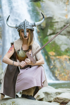 Beautiful blonde viking woman with a shield and a sword near a waterfall, Pruncea Casoca, Romania