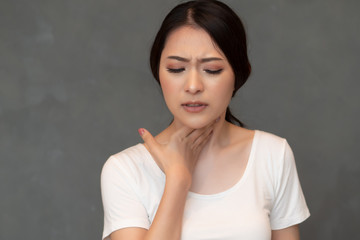 sick woman with sore throat portrait; sick asian woman with sore throat, cold, flu, contagious disease, virus outbreak, coronavirus, COVID 19, health care concept; young adult asian woman model