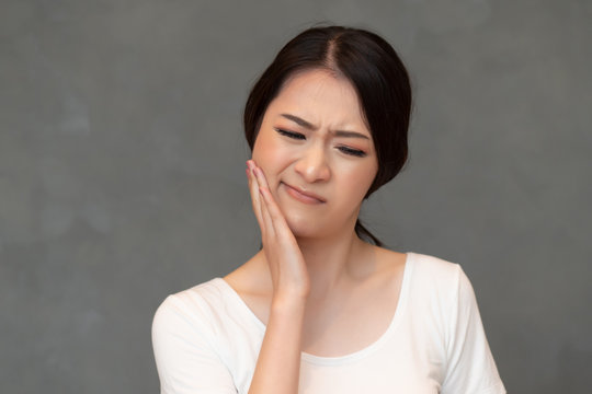 woman with toothache; sick asian woman suffering from toothache, tooth decay, tooth sensitivity, wisdom tooth pain, cavity, dental care concept; young adult asian woman model