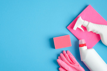 House cleaning service concept. Cleaning supplies on blue background. Flat lay pink sponge, rubber gloves, napkin and cleaner bottles.