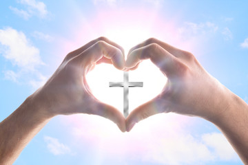 Hands forming a heart in heaven with spikes surrounding cross Fotomurales