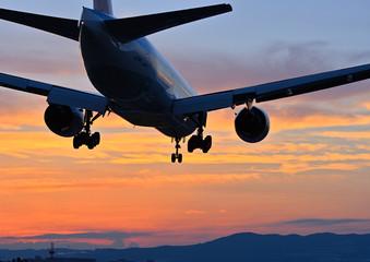 夕焼けの中で着陸態勢の旅客機