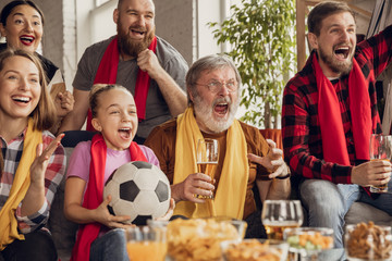 Excited, happy big family watching football, soccer match on the couch at home. Fans emotional cheering for favourite national team. Having fun from grandparent to children. Sport, TV, championship.