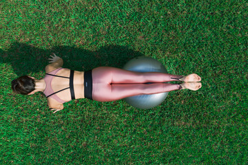 Sporty young woman doing stretching exercise with a ball in a dress field, balance posture. Beautiful athletic girl practicing yoga or pilates.