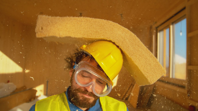 PORTRAIT: Funny shot of a smiling builder getting hit with a thick piece of foam