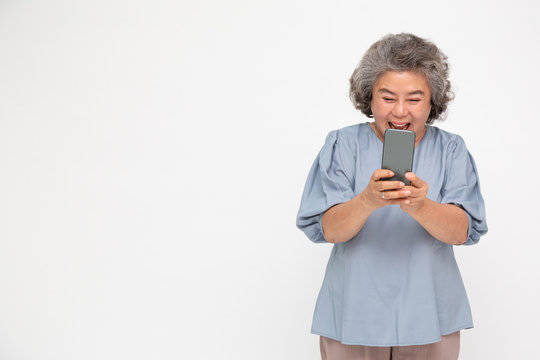 Asian senior woman using smartphone and receiving good news from the message on mobile chat application over white background